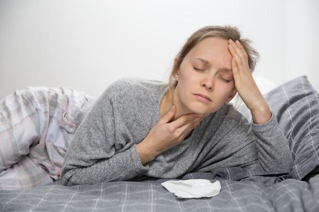 喉の痛みを持って目を閉じてベッドで疲れて病気の女性