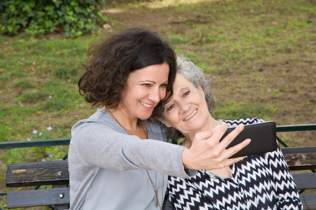 Веселая мать и дочь, принимая селфи
