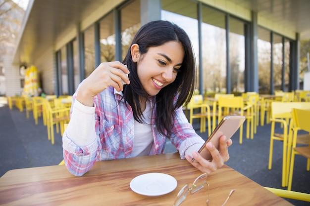 スマートフォンを使用して、カフェでコーヒーを飲みながら陽気な女性
