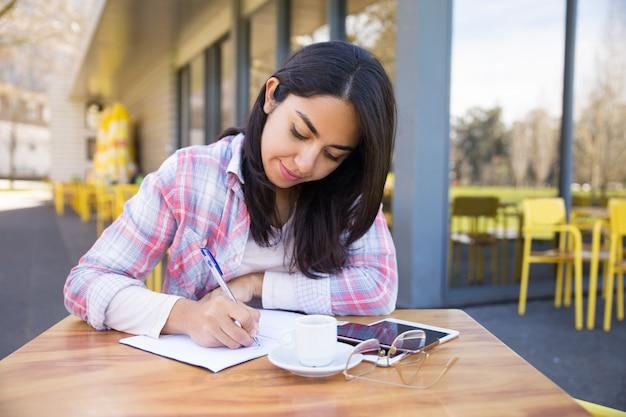 屋外カフェでメモを作る若い女性に焦点を当ててください。