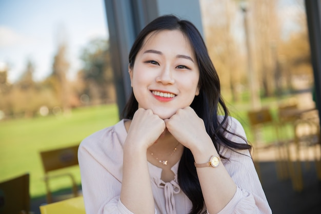 Радостная азиатская туристка отдыхает на террасе отеля