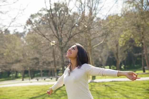 Радостная беззаботная девушка наслаждается отличной погодой