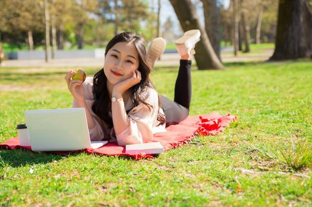 Расслабленная азиатская женщина держа яблоко и используя компьтер-книжку на лужайке