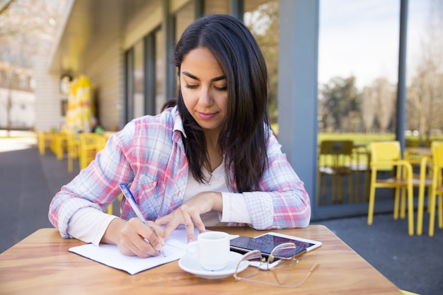 深刻な女性の屋外カフェでメモを作る