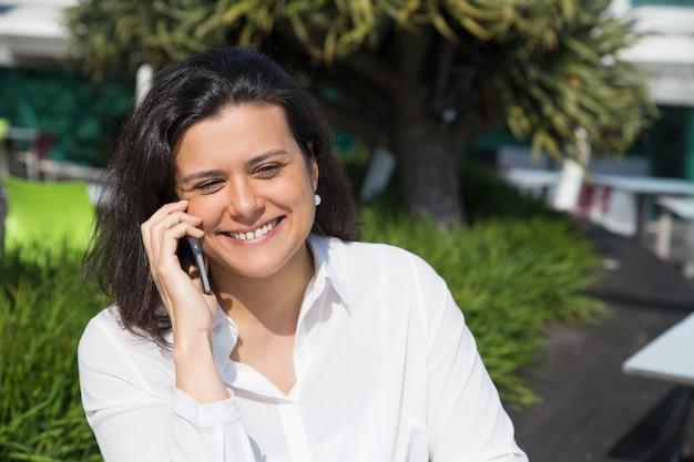 Улыбаясь привлекательная женщина разговаривает по мобильному телефону на открытом воздухе