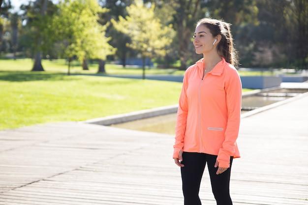 都市公園でリラックスした笑顔のスポーティな女性