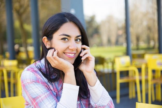 屋外カフェで携帯電話を呼び出す女性の笑みを浮かべてください。