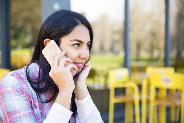 屋外カフェで携帯電話で話している女性の笑みを浮かべてください。