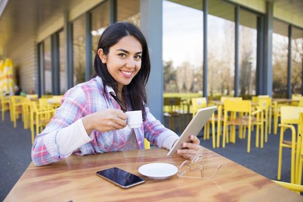 ガジェットを使用して、カフェでコーヒーを飲む女性の笑みを浮かべてください。
