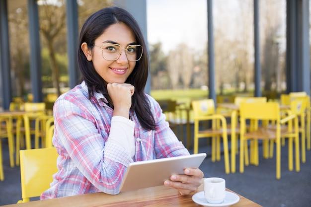 タブレットを使用して、カフェでコーヒーを飲む女性の笑みを浮かべてください。