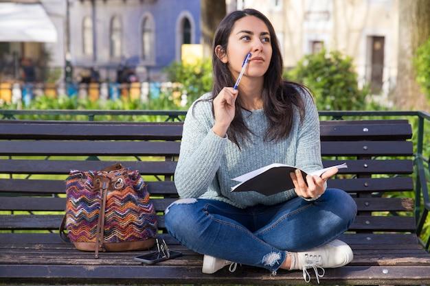 思いやりのある女性のノートを作ると屋外のベンチに座っています。