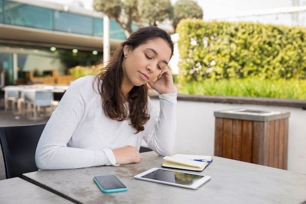 Утомленная молодая женщина сидя на кафе и изучая или работая