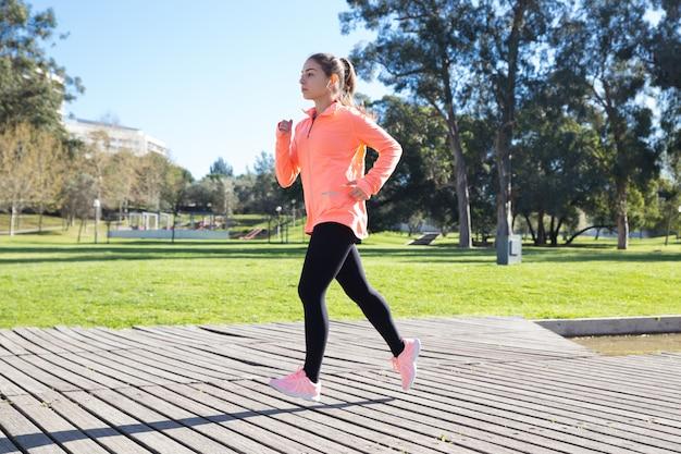 都市公園でジョギングする若い魅力的な女性