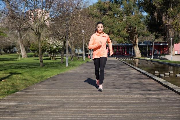 Молодая красивая женщина, бегом в городском парке