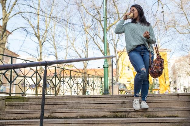 街の階段を降りて、コーヒーを飲む若い女性