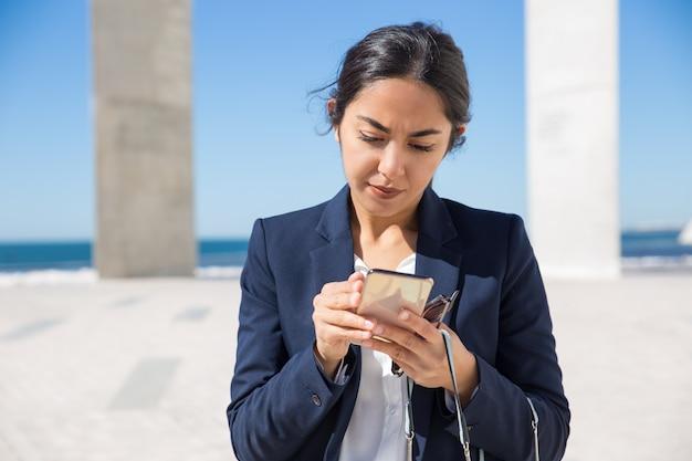 Сосредоточенный офисный помощник читает на экране телефона