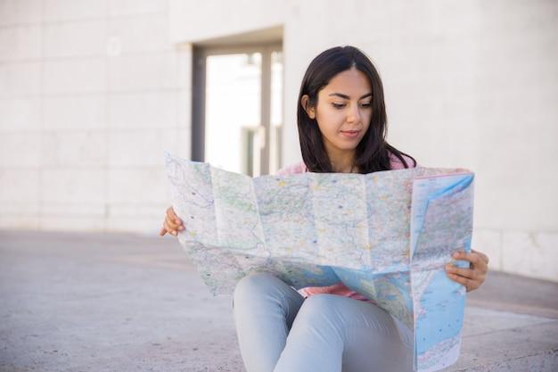 屋外の紙の地図を勉強して焦点を当てた若い女性