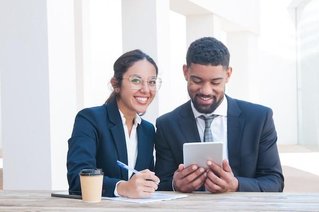 Счастливые бизнесмены используя таблетку и работая на столе