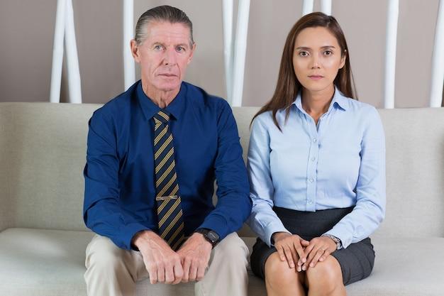 オフィスロビーに座って深刻なビジネス旅行者