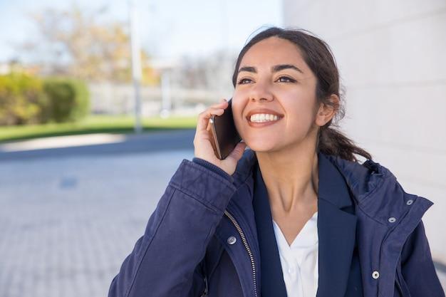 素敵な電話での会話を持つ幸せな陽気なマネージャー