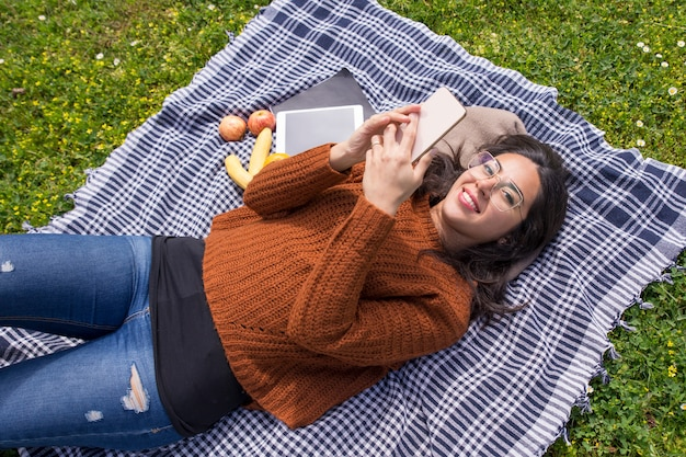 幸せな学生の女の子が草の上に横たわる