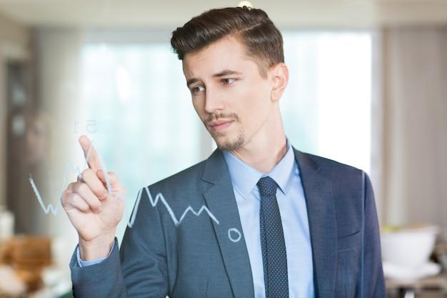 深刻なビジネスマンは、ガラス上のグラフにポインティング