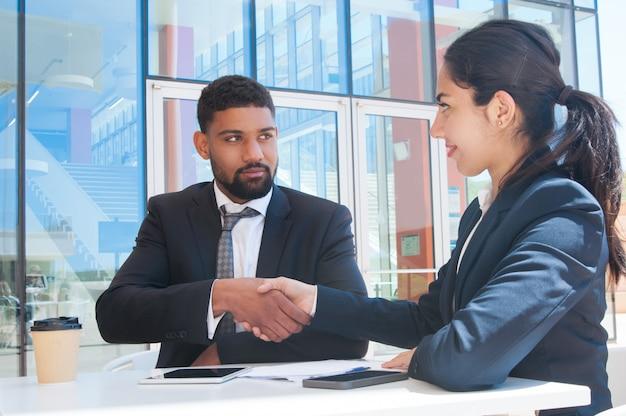 Серьезные деловые люди пожимают друг другу руки в кафе на открытом воздухе