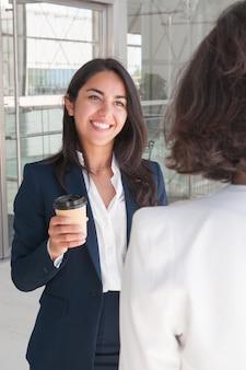 話しているとコーヒーを飲むビジネス女性の笑みを浮かべてください。