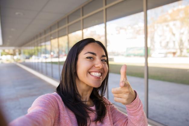 Улыбается женщина, принимая селфи фото и указывая на вас на открытом воздухе