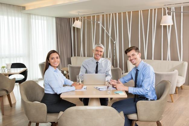 カフェでミーティングを持つ笑顔ビジネス旅行者
