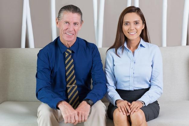 オフィスロビーに座って笑顔ビジネス旅行者