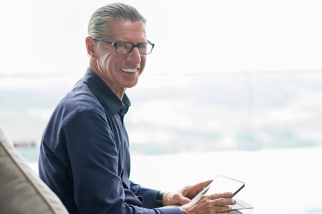 デジタルタブレットを使用してハッピーシニア男を笑顔