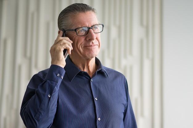 スマートフォンで話す笑顔シニアビジネスマン