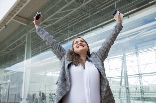 屋外の腕を上げる陽気なビジネス女性
