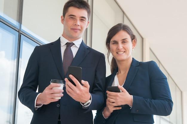 スマートフォンと陽気な自信を持っているビジネスマン
