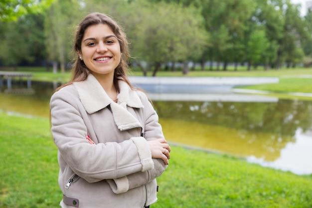 Жизнерадостная милая ученица колледжа позирует в парке