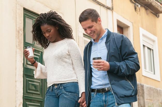 陽気な若いミックスレースのカップルが屋外で歩く