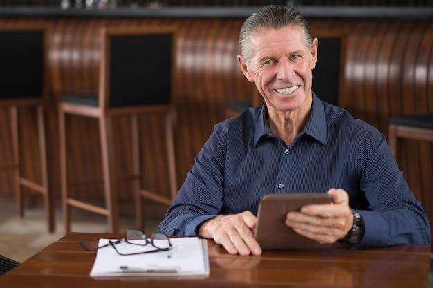 カフェでデジタルタブレットと笑顔シニア男