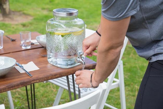 Крупным планом человека лить лимонад из дозатора на открытом воздухе