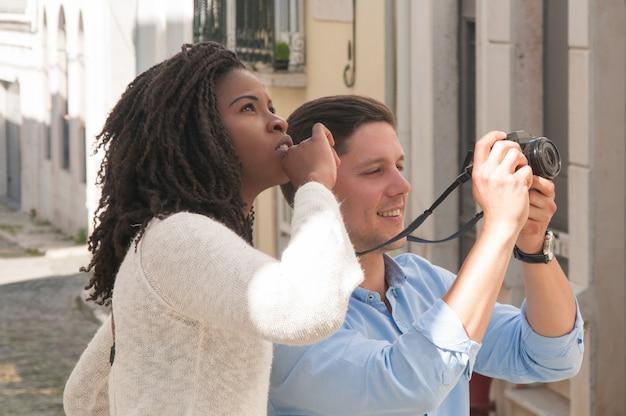 興奮したミックスは写真を撮る観光客のカップルを競いました