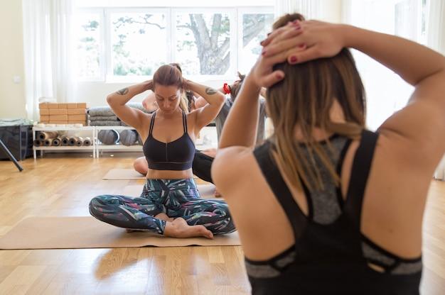 蓮のポーズで座っているヨガをやっている焦点を当てた女性