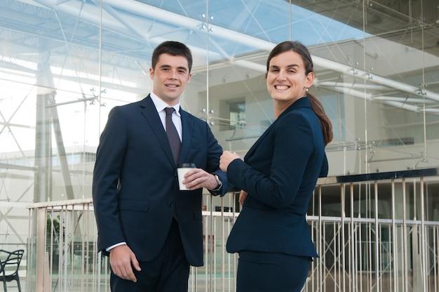 コーヒーを飲みながら屋外でポーズをとって幸せなビジネス人々