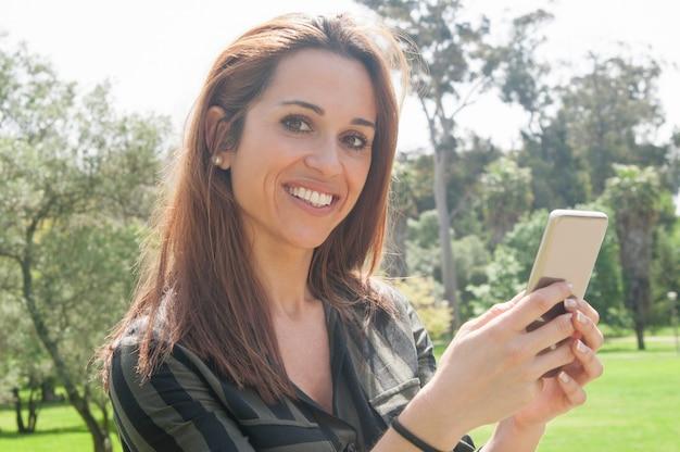 Счастливая жизнерадостная леди с помощью смартфона на открытом воздухе