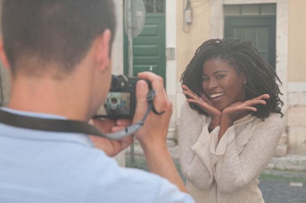 Человек принимает фото улыбающегося негритянка в городе