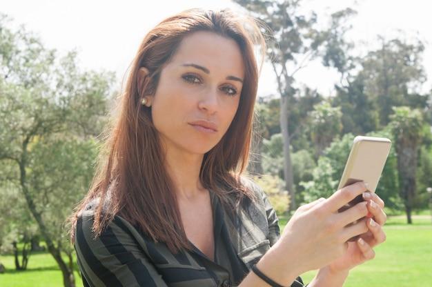 Задумчивая красивая леди, использующая мобильный телефон на открытом воздухе