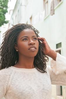 Мечтательная черная девушка прогуливается по аллее города