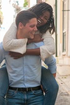 遊び心のある若い男が屋外の背中にガールフレンドを運ぶ