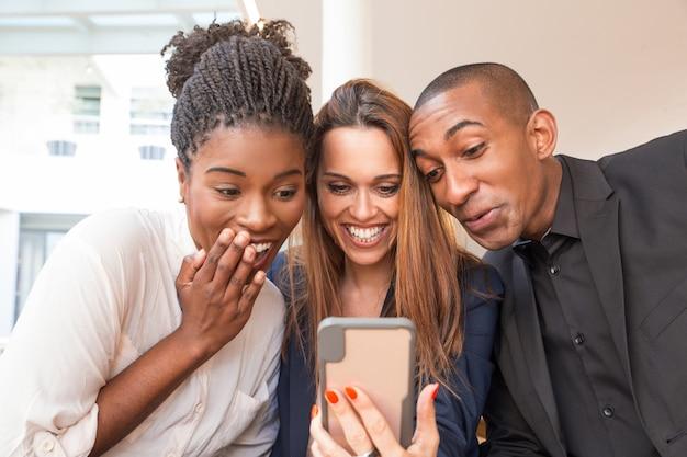 Портрет трех счастливых деловых людей, смеющихся над мобильным видео
