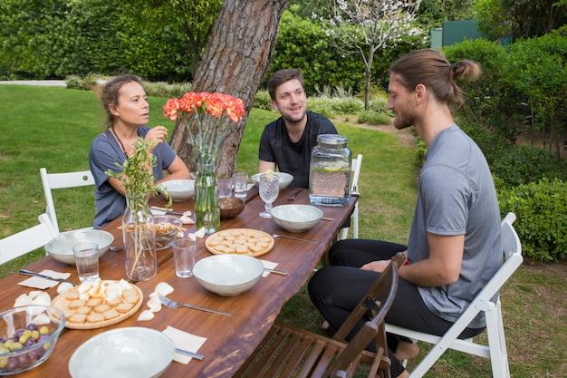 裏庭の木製のテーブルで朝食を食べて肯定的な人々
