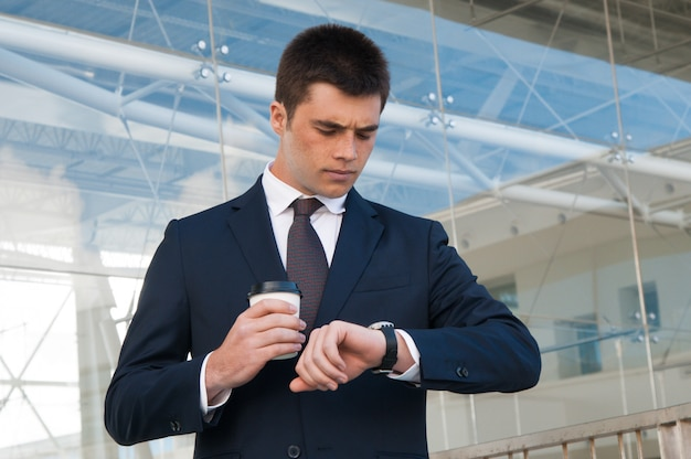 深刻なビジネスの男性が屋外の時計の時間をチェック
